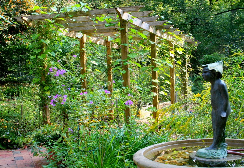 While Strolling Through A Large Garden, You May Find Yourself Pausing At A  Small Bench Beneath A Roof Of Vines Or Flowers Before You Continue On Your  Way.