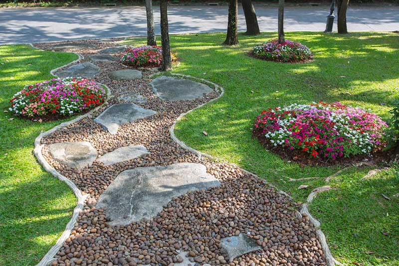 If you love stone garden paths as much as we do, you'll know that they do best when framed with a well manicured lawn or garden. This landscape makes the best of both worlds by dotting the surrounding grass with little islands of color in the form of impatiens.