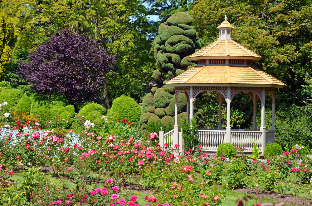 With its railings and support arches done up like an ornate porch fence, this gazebo looks ready to impress. Topped with a light natural wood tile roof in three layers, with a bespoke peak at the top, it's a subtly complex structure that stands out in stark elegance amidst a garden. A gazebo like this might be best designed to match the roof of your home.