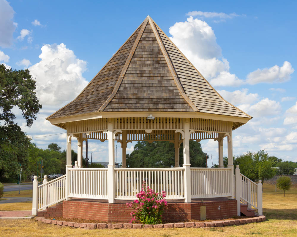The high-peaked roof on this bespoke gazebo gives it an instant sense of charm and style, standing out among the sparse trees on this flat landscape. Built over a charming red brick foundation, wrapped in a slim garden lined with more red bricks, we see the white fencing and columns rise toward the sharply angled roof. It's a more ostentatious gazebo, perfect for luxurious landscapes.