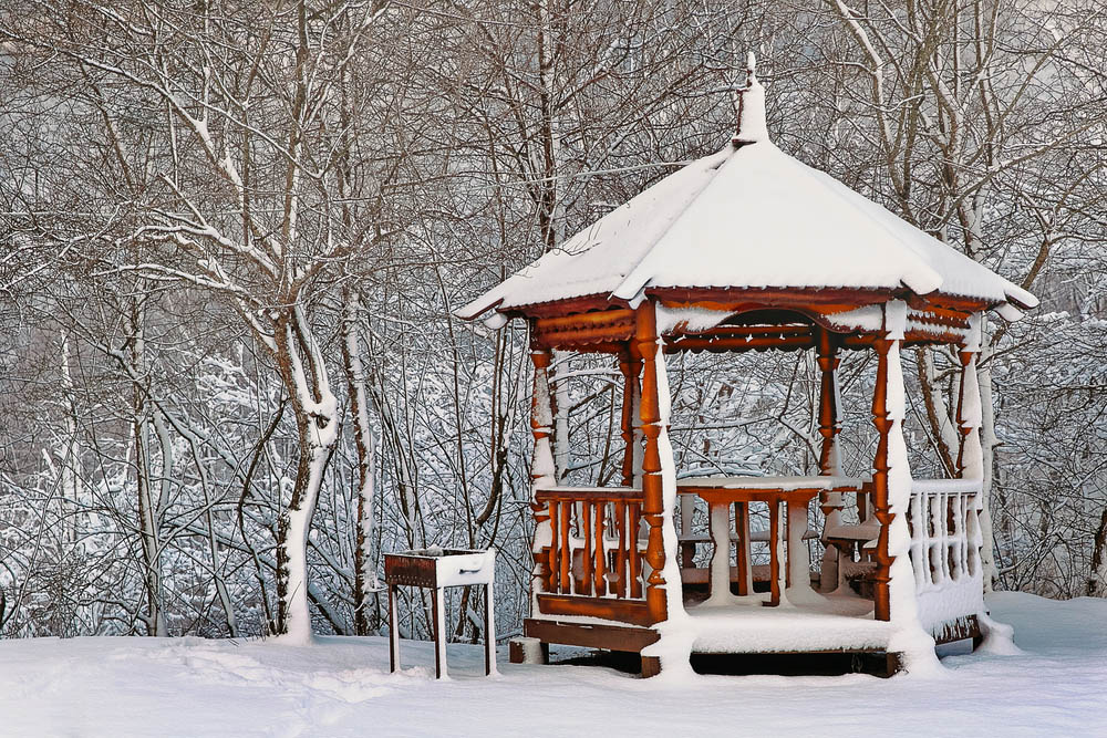 While this gazebo flaunts its rustic charm, with rich wood tone and ornately carved columns we see it bringing a spot of warmth and brightness to the stark winter landscape. Even covered by snow, it stands out with its welcoming curves and built-in table at the center, surrounded by built-in bench seating.