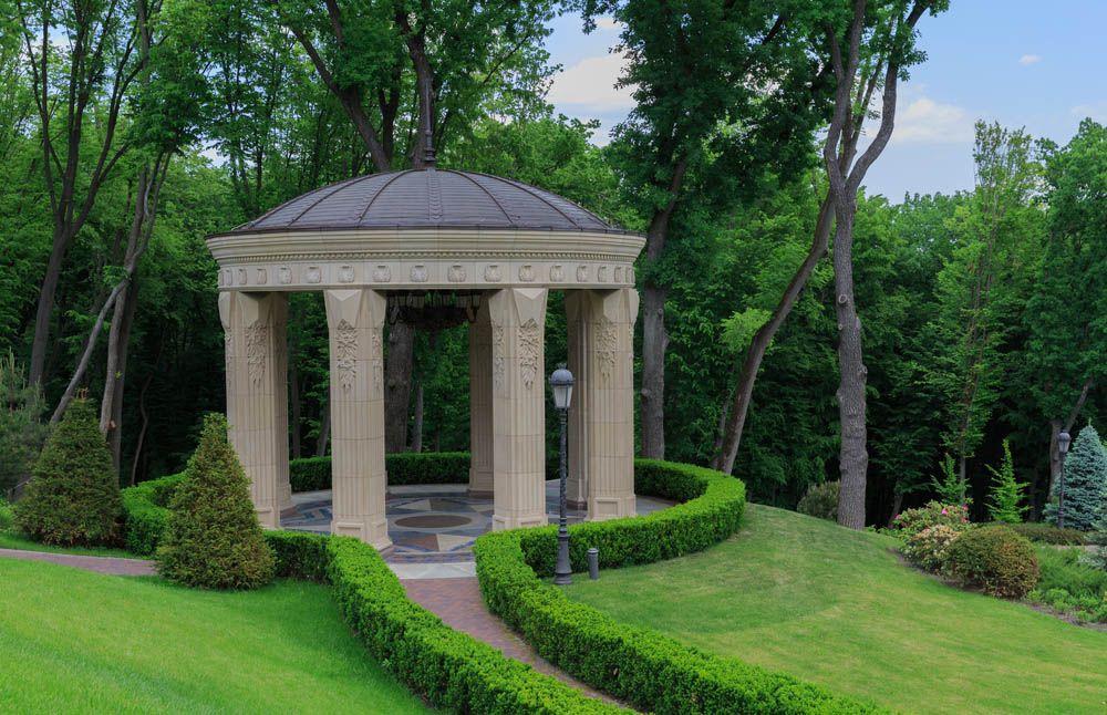 Alright, let's be honest. This gazebo isn't exactly meant for the average home or garden. It's an astounding piece of sculpture, a massive stone structure on intricately carved pillars, hanging over a grand marble floor design. The domed roof centers on a spike, and the entire structure is wrapped by neatly manicured bushes. It might be too rich for our blood, but it's inspirational nonetheless.