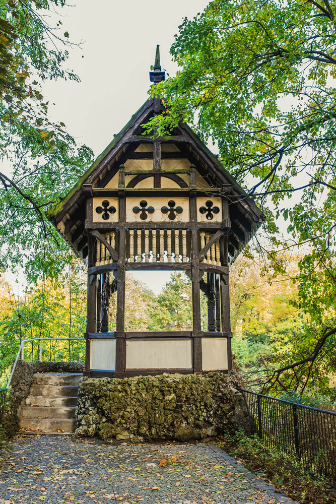While there's a large variety of gazebo styles out there, we don't often see Bavarian inspired models. This unique structure bears all the hallmarks of its inspiration, with a two-tone design of off-white panels and dark brown beams. Additionally, the roof structure is intricately crafted, while the foundation is set into a massive stone mound.