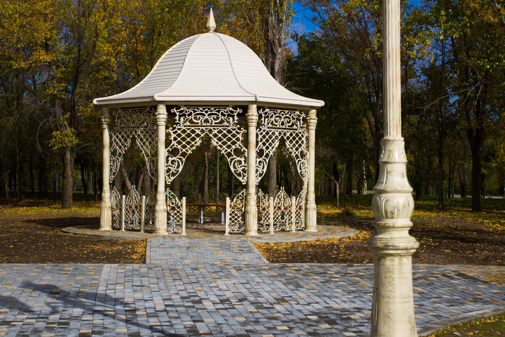 What stands out first, the bell roof or the ornate fencing? We can't decide, because this entire gazebo design has us transfixed. Standing atop a bespoke brick walkway, it's an extravagant, expertly crafted piece of art that just happens to provide shelter in the outdoors. This gazebo would work wonders in the backyard of any appropriately luxurious home or estate.