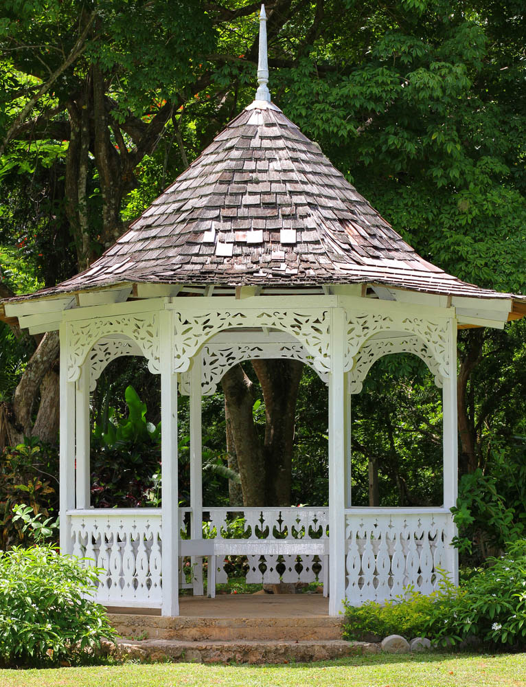 We love the ornate carving on the fence posts wrapping this gazebo, paired with the paper-cutout look of the arches between support pillars above. The pristine white paint contrasts with the earthen foundation, while the rustic wood roof adds a sense of timeless charm. It's topped with a unique spear design that helps it stand out.