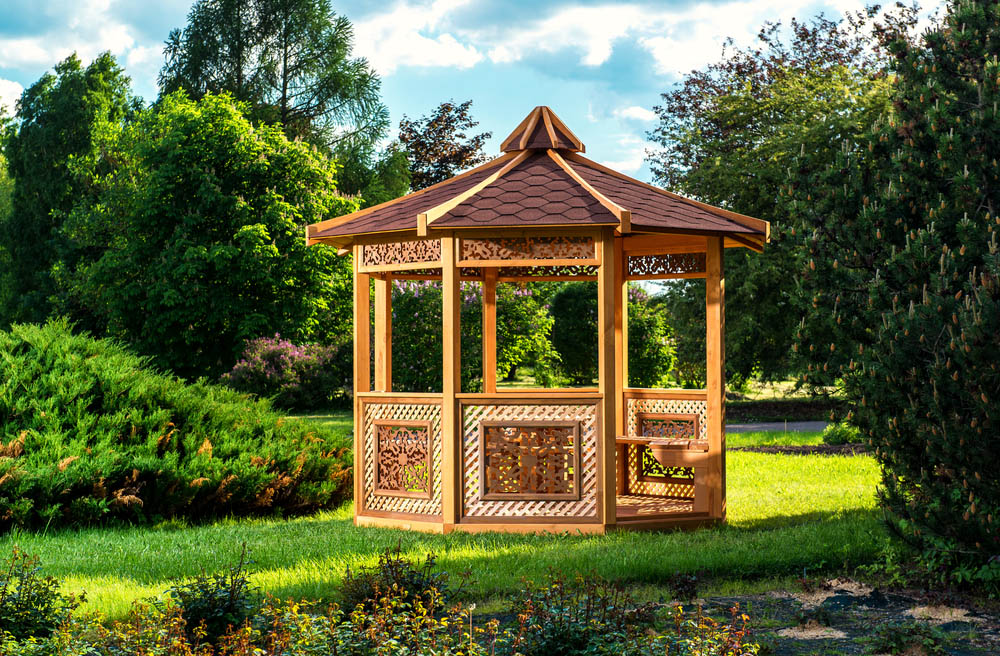 The obvious standout feature on this gazebo is the intricate wood carvings appearing on each side of the octagonal structure. Placed within the side fencing and between the support beams below the roof, these gorgeous carvings offer a unique bit of artistry in an unexpected place. The sumptuous roof design, with exposed beams, adds another layer of visual intrigue.