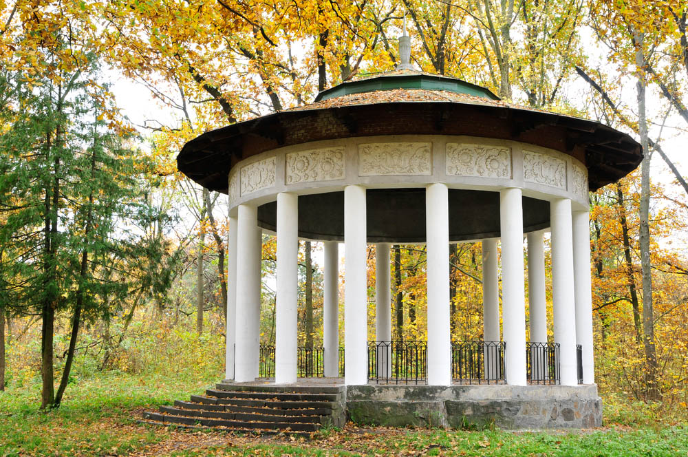 While we're used to seeing any and all manner of wooden gazebo designs, it's truly surprising to see one built from stone. This massive structure is wrapped in bespoke white pillars, supporting a tiered green roof over a concrete and stone base. Wrought iron fencing fills in the space between pillars, while the interior space is more than ample for a full dining party.