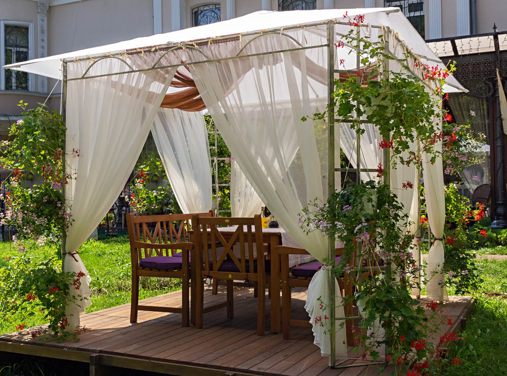 If having a thick, solid structure isn't the most important thing to you, a thinner metal gazebo might be the perfect fit. This model features trellis-like supports designed to hang flower baskets, and can be placed virtually anywhere because of its light weight. Here we see it set atop a rich wood base, but a gazebo like this can be planted right in your garden.