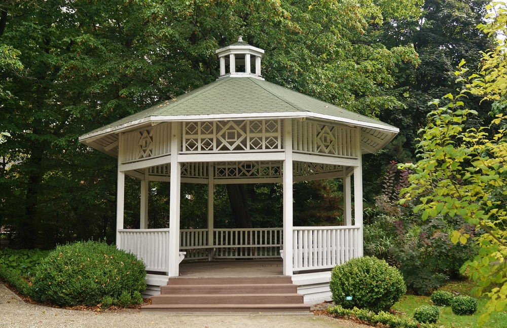 Similar to one of the more ornate gazebos pictured above, this gorgeous white model features intricate designs in the wood spanning between pillars. The geometric shapes give it a unique presence among other similarly built gazebo structures, while the small dome on the top of the roof adds another instance of intrigue. We love the wraparound bench seating built inside.