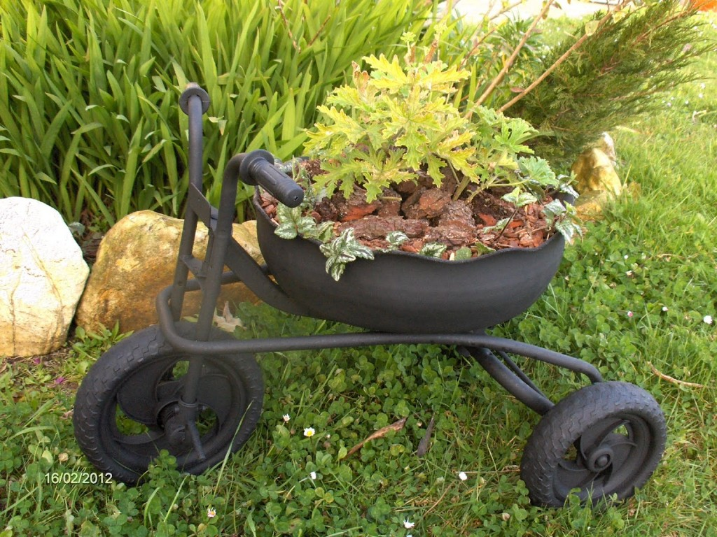 We love the rough and tumble look of this black painted tricycle planter. Its muted frame features matching dark wheels and centers on a massive bowl shaped container garden. This garden has been neatly filled with lush greenery, sprouting through large wood chips for a uniquely rugged look. We like the dark, unobtrusive look of the tricycle here, calmly making a novel place to plant.