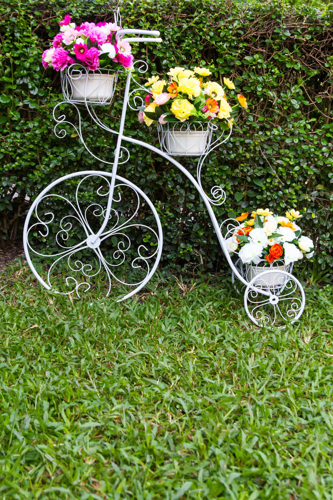 This rather elaborate tricycle sculpture is perfect for when you're trying to achieve that elegant, stately look in a garden. The finely detailed metal work in the wheels reflects the delicate flowers that are meant to grow on it, while the trio of baskets provides plenty of space for those flowers to go. The white frames mean that it will allow any flowers to truly pop, unobtrusively adding a layer of beauty and fun.