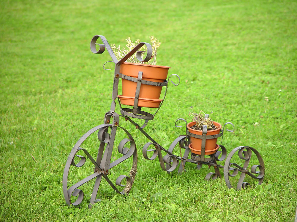 For our second example, we're kind of cheating. Please don't tell! Instead of reusing an old tricycle, this project simply involves placing your planters into a purpose-built tricycle-shaped container garden sculpture. Those wheels might be hard to actually ride on, but they sure look the part. The ornate curves and built-in planter holders make it a worthy garden accessory, upcycled or not.