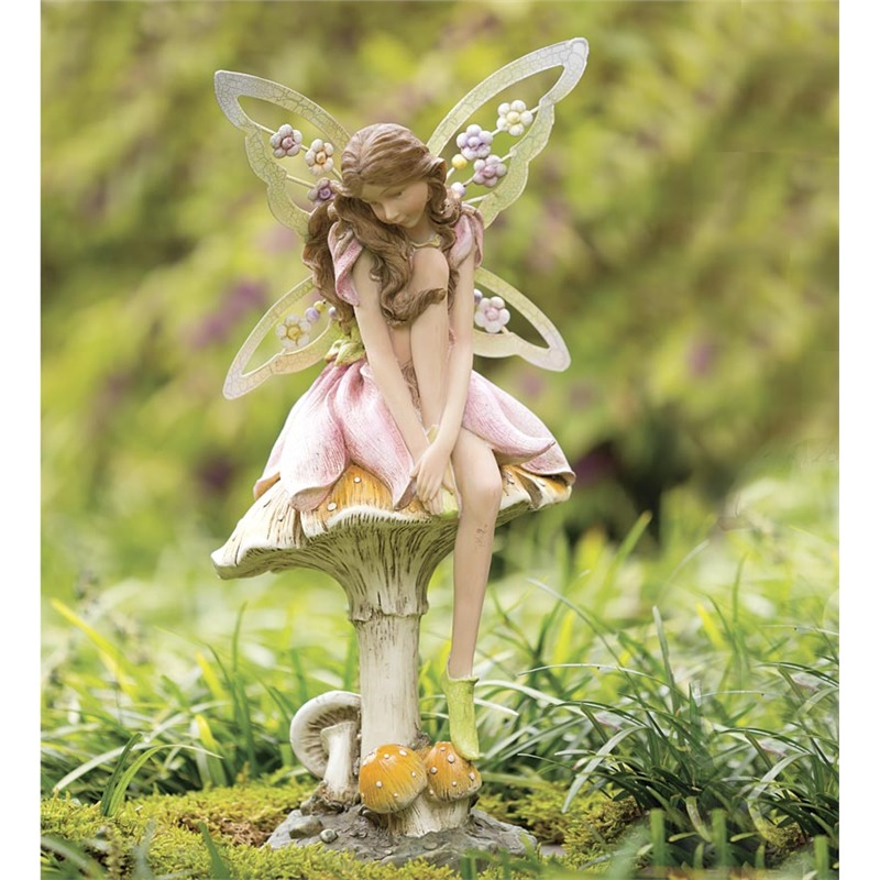 """There's something intrinsically fun about calling a mushroom a """"toadstool,"""" so we couldn't resist, especially when this one is topped by a delicately carved, subtly colored fairy sculpture. The wings feature tiny flowers of their own, perfect for close-up examination. Place this deep in the garden, or right on the patio."""