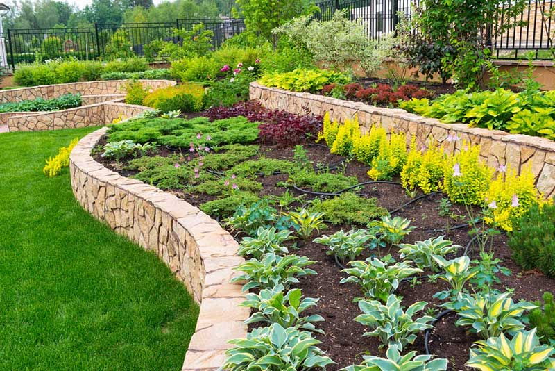 "When you're doing a heavy landscaping project that involves reshaping the earth, you're already ""going big"" so why not consider the possibilities of using well shaped stone walls to create tiered gardens? This is a major project but one with timeless value and appeal. The stones can be chosen for their shape, color, or ease of use, and the distinct garden tiers can be used to place wildly different plant life."